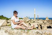 Girl Sits On A Rock Amid The Ruins Of Carthage In Tunisia