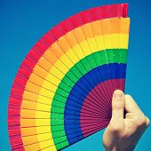 someone holding a hand fan painted with the colors of the gay pride flag over the blue sky, with a r