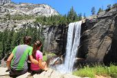 Hikers resting in Yosemite National park enjoying view of beautiful waterfall, Vernal Fall. Young hiking couple relaxing after hike in beautiful summer nature landscape.