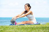 Woman training fitness stretching legs exercise outside by the ocean sea. Beautiful fit female fitne
