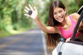 Car - woman showing new car keys smiling happy on road trip after getting drivers license. Beautiful