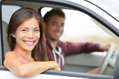 Cars - couple driving in new car smiling happy looking at camera. Young people on road trip drive in car. Beautiful interracial couple in their twenties, Asian woman, Caucasian man.