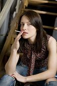 Young Attractive Smoking Girl In Jeans Having A Hole Sitting On Stairs. Bad Habit