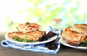 Pizza calzones on plates on nature background