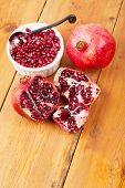 Pomegranate Pips In A Bowl With Whole Fruit On Wooden Surface