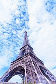 Eiffel Tower against the blue sky and clouds
