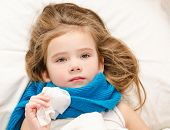 Sick Little Girl Lying In The Bed With Scarf And Tissue