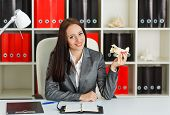 image of workplace safety  - Businesswoman with a model of plane sits on a workplace in the office - JPG