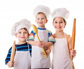 stock photo of apron  - Three young chefs with ladle and rolling pin - JPG