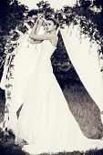 foto of wedding arch  - Beautiful elegant bride stands under the wedding arch - JPG