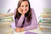 Smiling student girl sitting between stacks of books purple background
