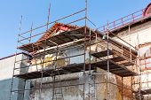 stock photo of scaffold  - Scaffolding covering a facade of an old building under restoration - JPG