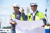 stock photo of engineering construction  - Two engineers at construction site are inspecting works on site according to design drawings - JPG