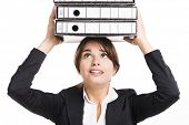 Beautiful business woman tired of work and carrying lots of folders on hands, isolated over white ba
