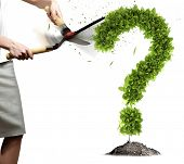 Young businesswoman cutting plant shaped like question mark