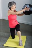 Middle Aged Female Sports Trainer With Medicine Ball