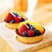 fruit tarts shot with selective focus on wood board
