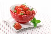 Bowl with fresh strawberries on a ground with small hearts