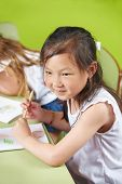 Chinese girl drawing with crayons in a kindergarten group