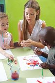 Children painting with tempera color in kindergarten and a nursery teacher is helping