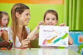 Girl showing self drawn painting in kindergarten with nursery teacher