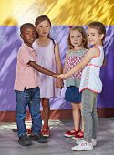 Interracial group of children learning dancing in a school class