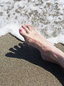 Woman Feet Relaxing On The Shore Waiting For The Sea Foam