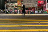 HONG KONG - MAY 11, 2014: Pedestrians wait to cross the street in the district of Mong Kok in Hong K
