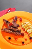 grilled beef meat with berries fried potatoes and cherry under sweet honey sauce on orange plate ove
