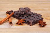 split bar of dark chocolate on wooden table