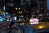 Taxi in the night, Hong Kong, Asia. The Chinese words in the top of car is meaning