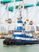 MIAMI,USA - MAY 27,2014 : Tugboat sailing in the Port of Miami with containers and cranes on the bac