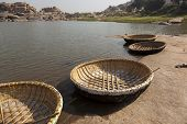 Round stereotypic boats and hills with amazing stones at Hampi temple complex in India
