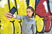 Happy attractive girl with smart phone takes photo of herself against urban grunge graffiti wall, to