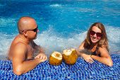 stock photo of hot-tub  - Couple with coconut drink relaxing in hot tub - JPG