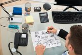 Businessman Planning Strategy On Paper At Desk