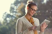 image of knitwear  - closeup of happy woman in glasses using tablet pc in the park - JPG