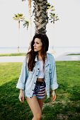Charming hot hipster girl standing on the beach looking away