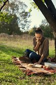 Trendy Girl Enthusiastically Reading A Book And Eating An Apple During The Picnic. Sitting Near The