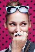 Closeup Of Smiling Trendy Girl Showing Mustache On Pink Background