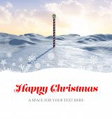 Happy Christmas against snowy land scape with pole