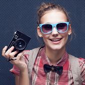 Smiling Hipster Girl With Vintage Camera. Trendy Teenager In Checkered Red Shirt And Bow-tie And Sun