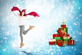 Happy brunette jumping and holding his scarf against christmas tree shape on blue shimmer