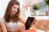 Cute teenage girl reading novels on ebook reader while sitting on the couch
