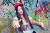 Trendy Beautiful Long Haired Model Posing On Graffiti Background. Blow Bubblegum And Show Thumb Up.