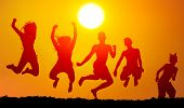 Silhouettes of boys and girls jumping on the beach on sunny summer day