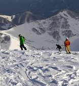 Snowboarders And Skier On Off-piste Slope In Sun Evening
