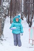 Happy Kid Girl Child Outdoors In Winter Digging Snow With Toy Spade