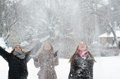 Three Teenage Girls Throwing Snow In The Air