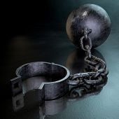 picture of ball chain  - A vintage ball and chain with an open shackle on a dark backlit studio background - JPG